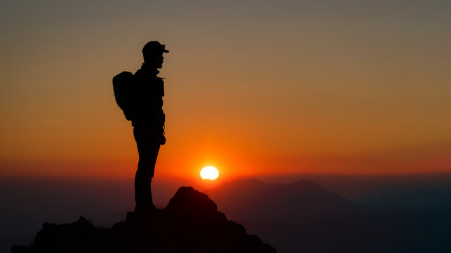 Mountaineer on the top of the mountain watching the fantastic sunset
