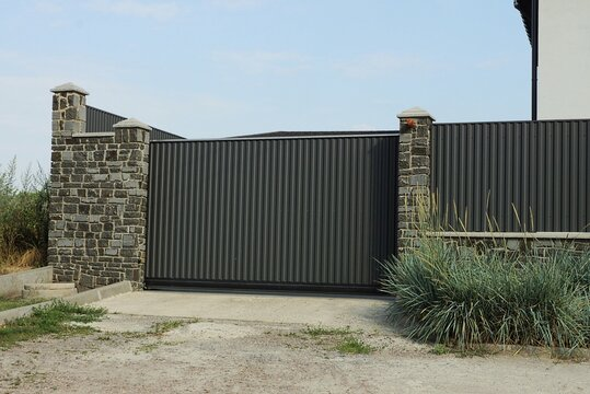 one black metal gate and part of the wall of a fence made of gray stones and iron on the street