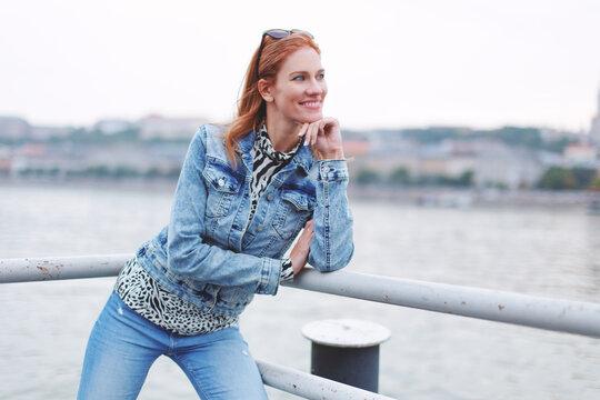 Positive redhead woman looking away at riverbank