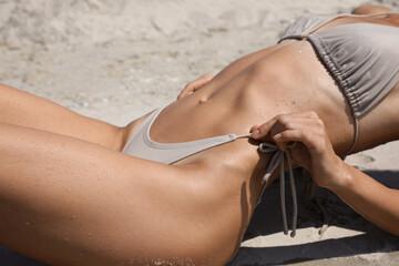Obraz Woman with perfect body in bikini on sandy beach, closeup - fototapety do salonu