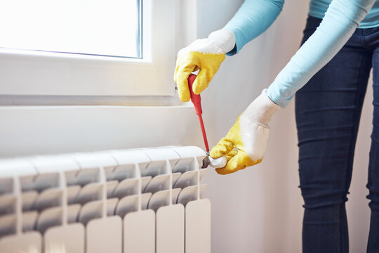 Handyman with gloves fixing and bleeding air from central heating gas radiator system at home.