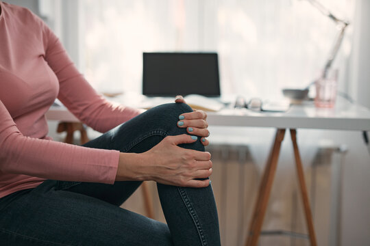 Woman with spasm, cramp, sprained, dislocated knee and joint pain, working from home troubles and issues.