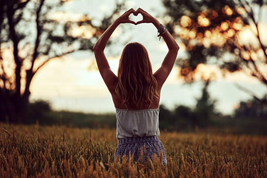 Woman in nature holding heart-shape symbol made with hands.
