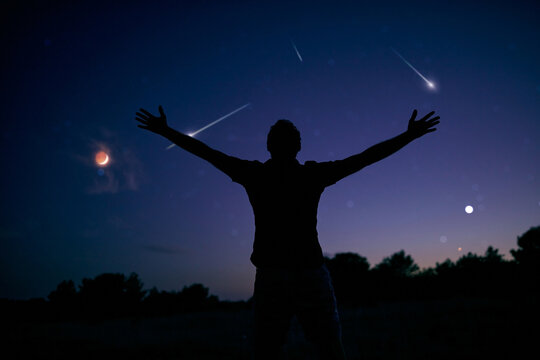 Silhouette of a man enjoying countryside under the starry skies.
