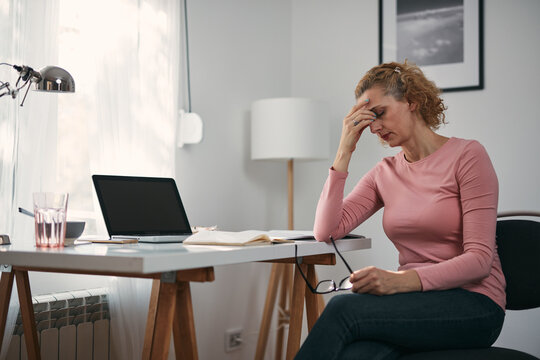 Woman with eyes hurting, sinus problem, headache, head pain, working from home troubles and issues.