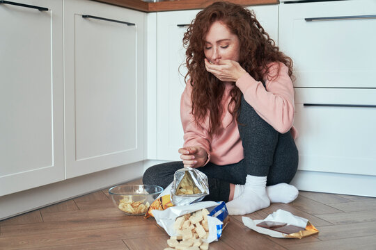 Young caucasian woman having eating disorder and eating greedily on the floor