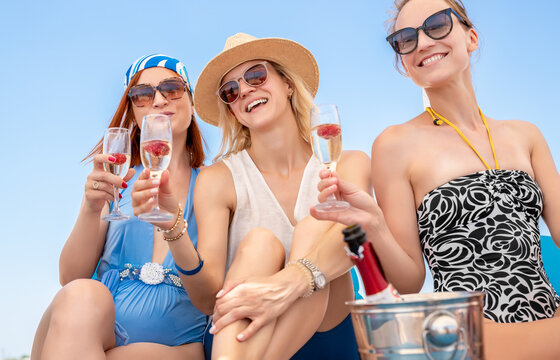 Portrait group of three young adult beautiful caucasian girlfriends enjoy drinking champagne cocktail celeberate bachelorette party event pool seaside beach on summer day. Friends cheers clink wine