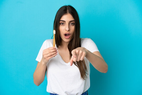 Young caucasian woman brushing teeth isolated on blue background surprised and pointing front