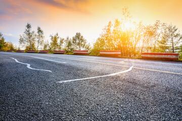 Empty asphalt road and autumn trees landscape at sunset.