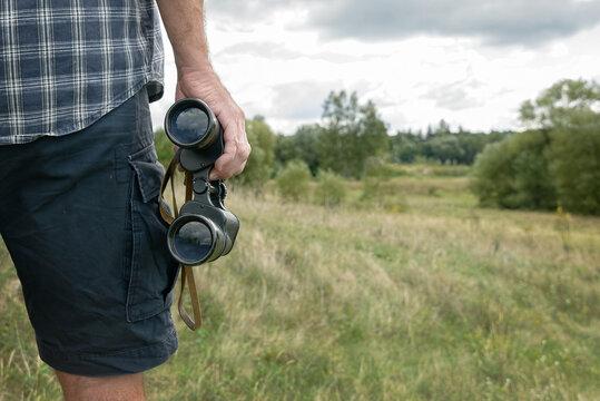 Man on the trail holding binoculars