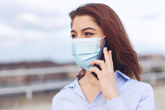 Young businesswoman calling outdoors during pandemic