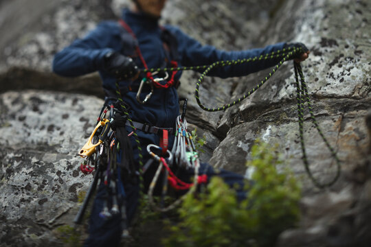 Climber works with a rope during the ascent, unsharp silhouette, face is not visible.