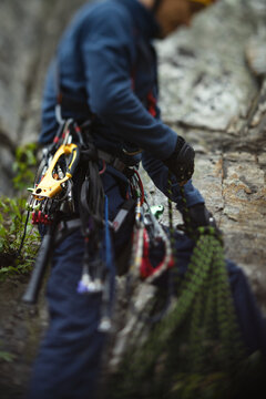 Climber works with a rope during the ascent, unsharp silhouette, close-up.