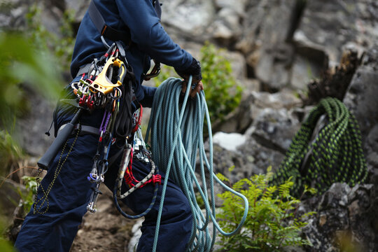 Climber works with a rope during the ascent, face is not visible.