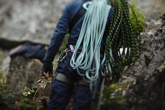 Silhouette of a rock climber with ropes, abstract unsharp image, rear view.