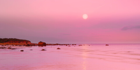 Full moon seascape in pink color at sunrise over the rocky beach on Cape Cod in October