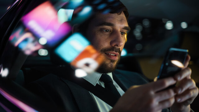 Handsome Businessman in a Suit Commuting from Office in a Backseat of His Car at Night. Entrepreneur Using Smartphone while in Transfer Taxi in Urban City Street with Working Neon Signs.