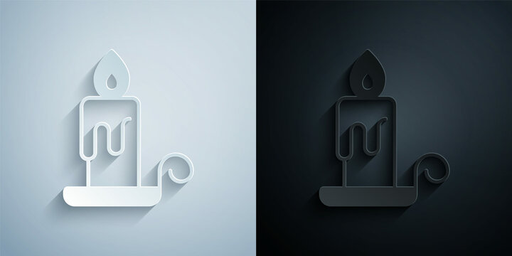 Paper cut Burning candle in candlestick icon isolated on grey and black background. Cylindrical candle stick with burning flame. Paper art style. Vector