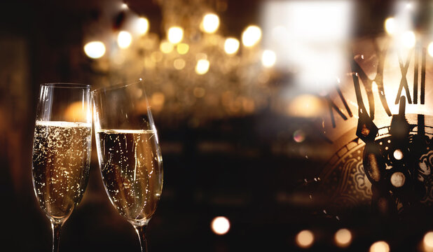New year countdown with a clock and champagne glasses. Dark new year's eve background with festive golden bokeh and space for text.