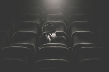 illustration of scared man covering his eyes with hands watching horror movie at the cinema alone, fear concept