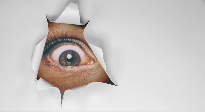 Eye peeking through peep hole watching something scary. Scared woman with look of horror in her eyes looking peeping from a dark room at night