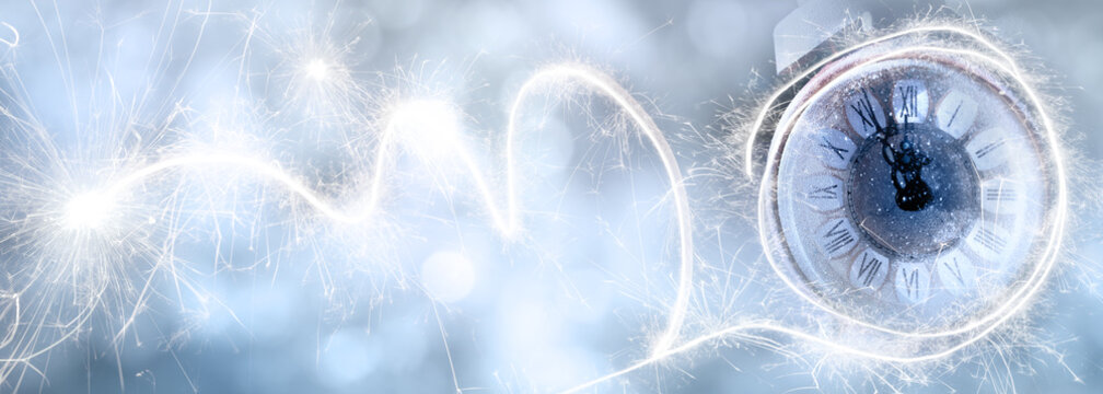 New year's eve countdown with alarm clock and sparklers on abstrakt ice blue bokeh background. Horizontal background for new year congratulations with space for text.