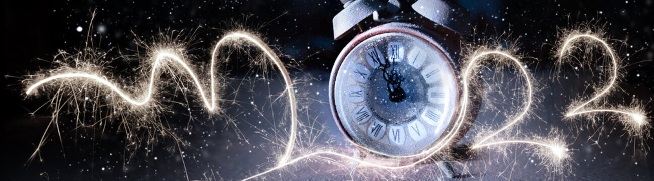 New year's eve 2022 countdown with alarm clock and fireworks in night sky. Horizontal background for new year congratulations.