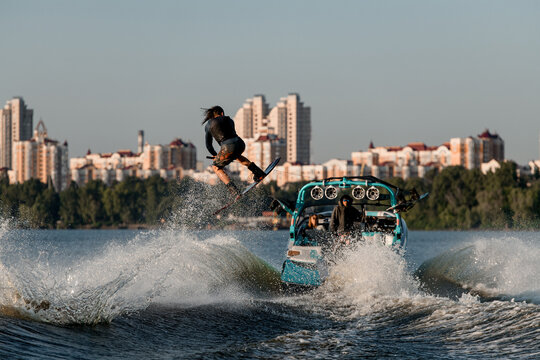 wakeboarder moving fast behind boat holding rope and jumping high on splashing river wave.