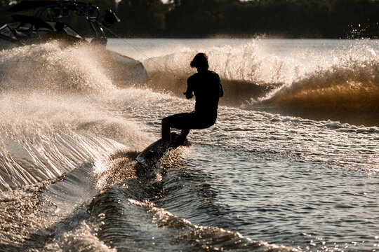 Back view of man riding wakeboard behind motor boat on splashing river waves. Wakeboarding and water sports