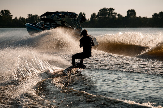 Rear view of energy man riding wakeboard behind motor boat on splashing river waves. Active and extreme sports