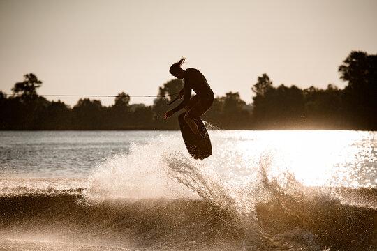 male wakeboarder masterfully jumping on wakeboard over splashing wave
