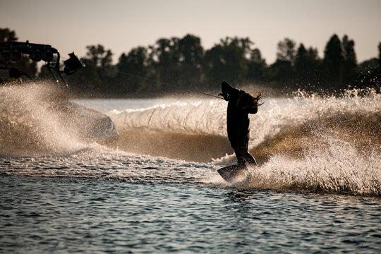 man holding rope and making trick riding wakeboard behind motor boat on splashing waves.