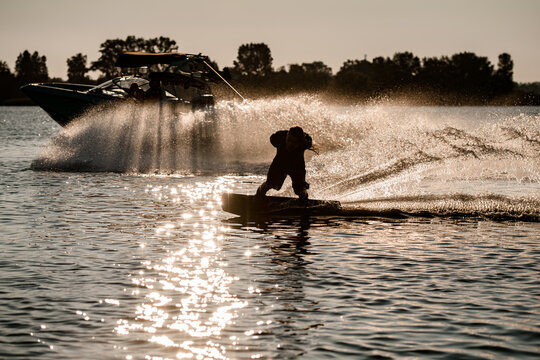 energy man holding rope and riding wakeboard and skillfully making trick behind motor boat on splashing river waves.