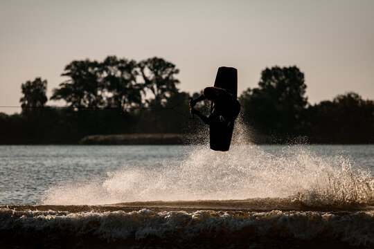 active male wakeboarder masterfully makes extreme stunts jumping and flips on wakeboard over splashing water
