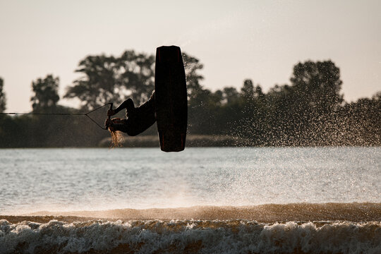 active male wakeboarder makes extreme stunts jumping and flips on wakeboard over splashing water