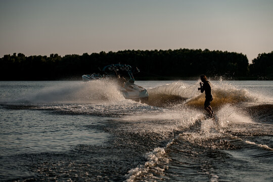 Great rear view of energy man riding wakeboard behind motor boat on splashing river waves. Active and extreme sports