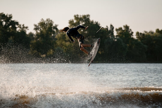 active man making trick in jump time with wakeboard and many splashes around