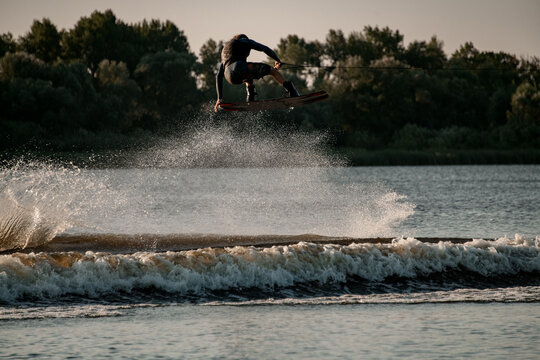 wonderful view of dynamic guy holding rope and jumping high with wakeboard over water