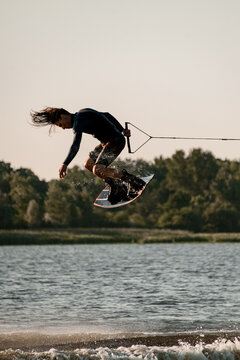 active man holding rope and making trick in jump time with wakeboard over water