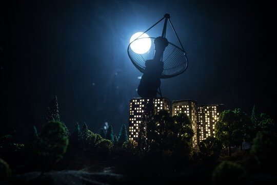 Silhouettes of satellite dishes or radio antennas against night sky. Space observatory or Air defence radar over dramatic night sky. Creative artwork decoration. Selective focus