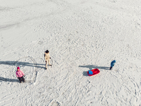Aerial top view Young adult mother wear jacket enjoy fun sledging two cute little sibling kids boy girl frozen white snow lake ice surface landscape bright sunny cold winter day. Outdoor activity
