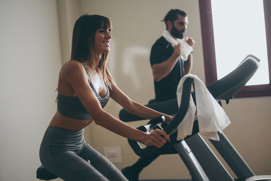 Determined young couple working out in gym. Fit boy and girl doing exercise with cyclette and tapis roulant. Beautiful sporty woman. Strong boys works out together. Wellness, health, sport, concept.