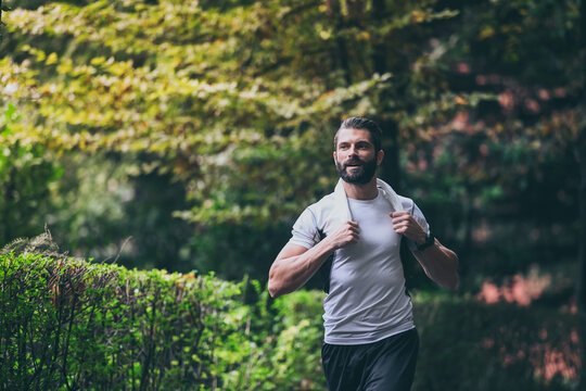 Determined young man running outside in the park. Fit boy doing exercise outdoor. Beautiful sporty male run alone. Sweaty athlete training with towel. Wellness, health, sport, fitness open air concept