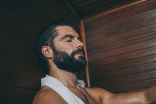 Beautiful healthy boy relaxing in a woden sauna. Young bearded man resting after workout in the gym. Fitness male with tatoo and white towel, laying on the bench in the spa. Wellness, health concept