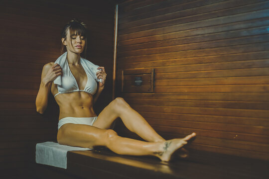 Beautiful healthy girl relaxing in a woden sauna with a white bikini. Young woman resting after workout in the gym. Fitness female with towel, laying on the bench in the spa. Wellness, health concept