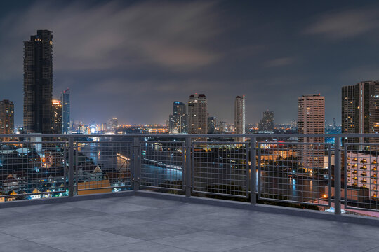 Panoramic Bangkok skyline view, concrete observatory deck on rooftop, night time. Asian corporate and residential lifestyle. Financial city downtown, real estate. Product display mockup empty roof