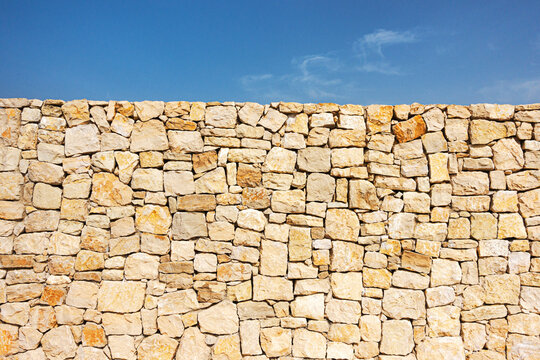 Old brown masonry wall of stones and blue sky background. Low angle view