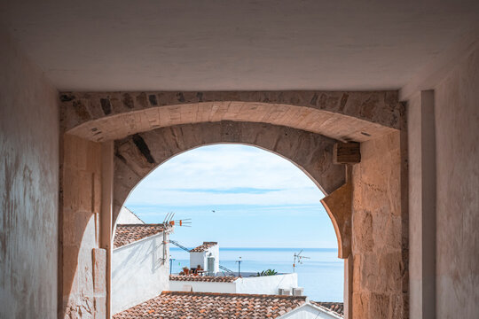 View from arch to Altea town white houses with tiled roofs and the Mediterranean sea at sunny day. Altea, Costa Blanca, Spain