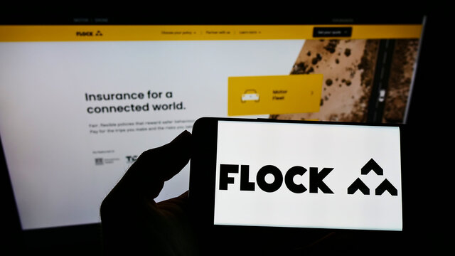 STUTTGART, GERMANY - Aug 02, 2021: Person holding smartphone with logo of UK insurance company Flock Ltd. on screen in front of website